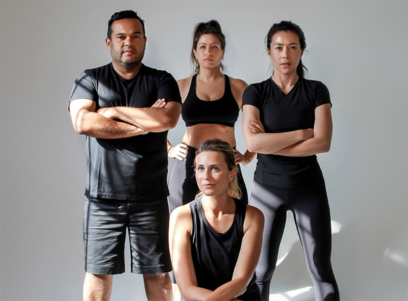 Four personal trainers posing in front of camera.